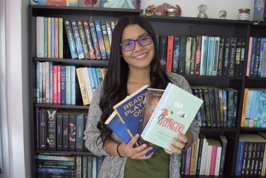 Jennifer Moreno en la estantería de su casa con los libros que fueron obsequios en una feria del libro organizada en Bogotá llamada Filbo.